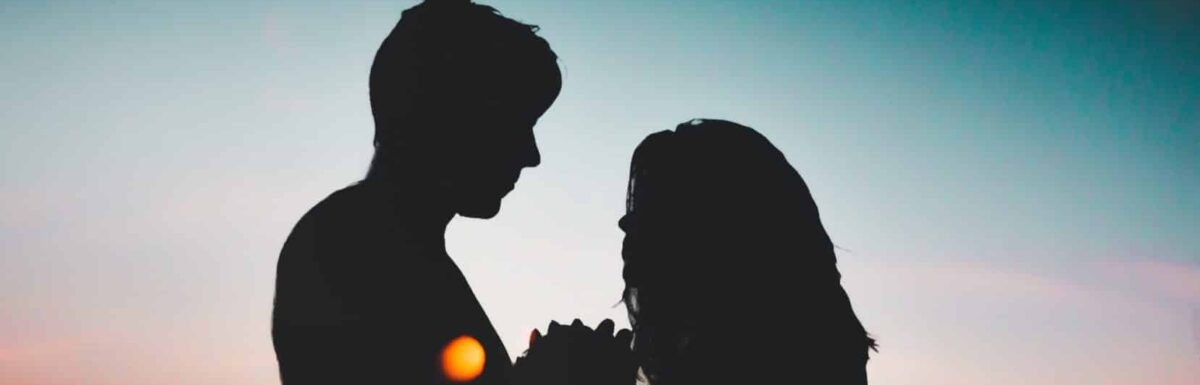 A silhouette of a young man and woman against the moonlight