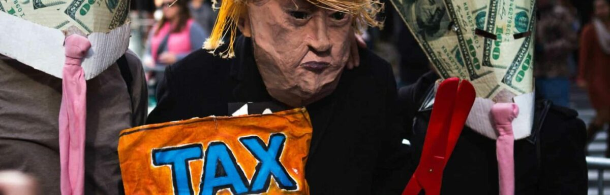 A person in a papier-mâché Donald Trump mask