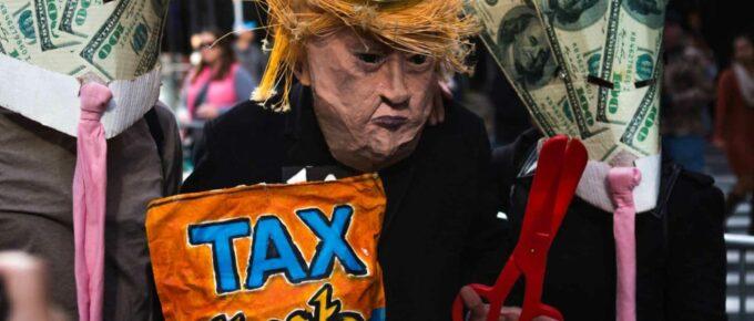 A person in a papier-mâché Donald Trump mask