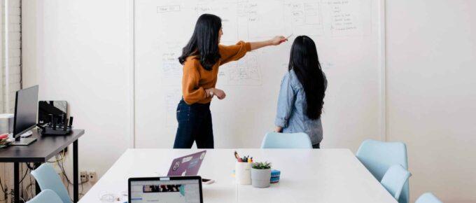 Businesswomen working at whiteboard