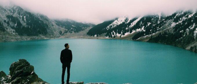 Man standing near lake, looking at horizon