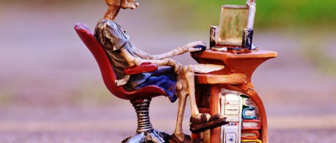 Sculpture of a skeleton sitting at a desk, using a computer