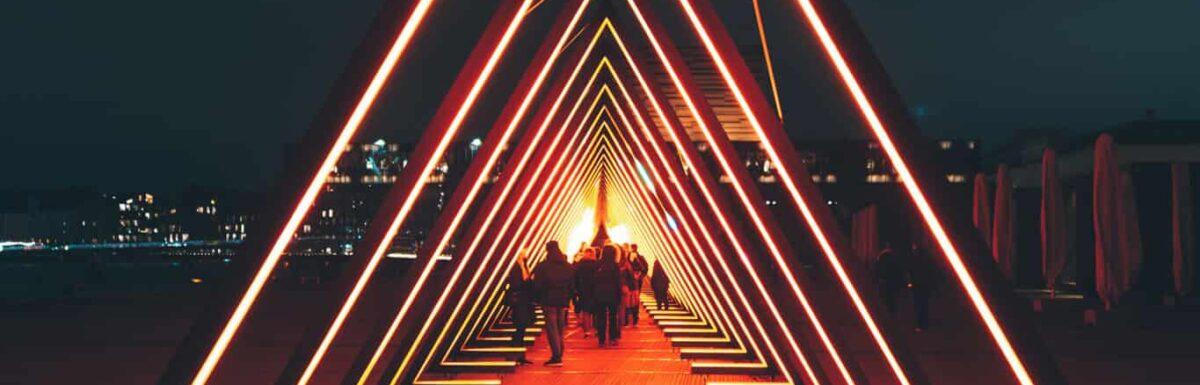 People walk down an artful red carpet