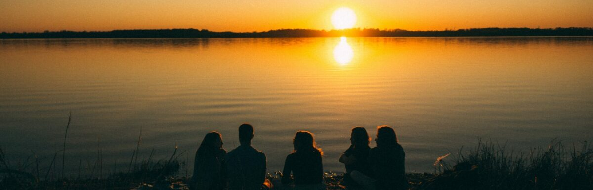 Five people sitting by water, watching sunset