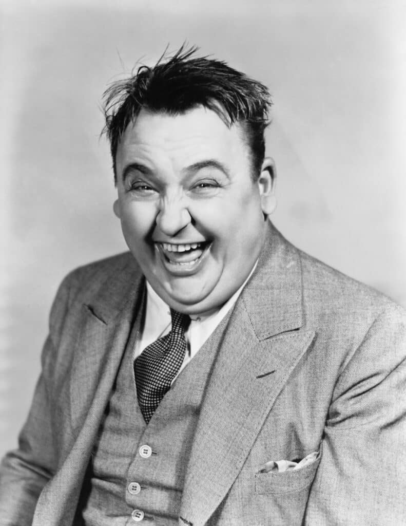 Black and white, vintage photo of a man in a suit laughing heavily