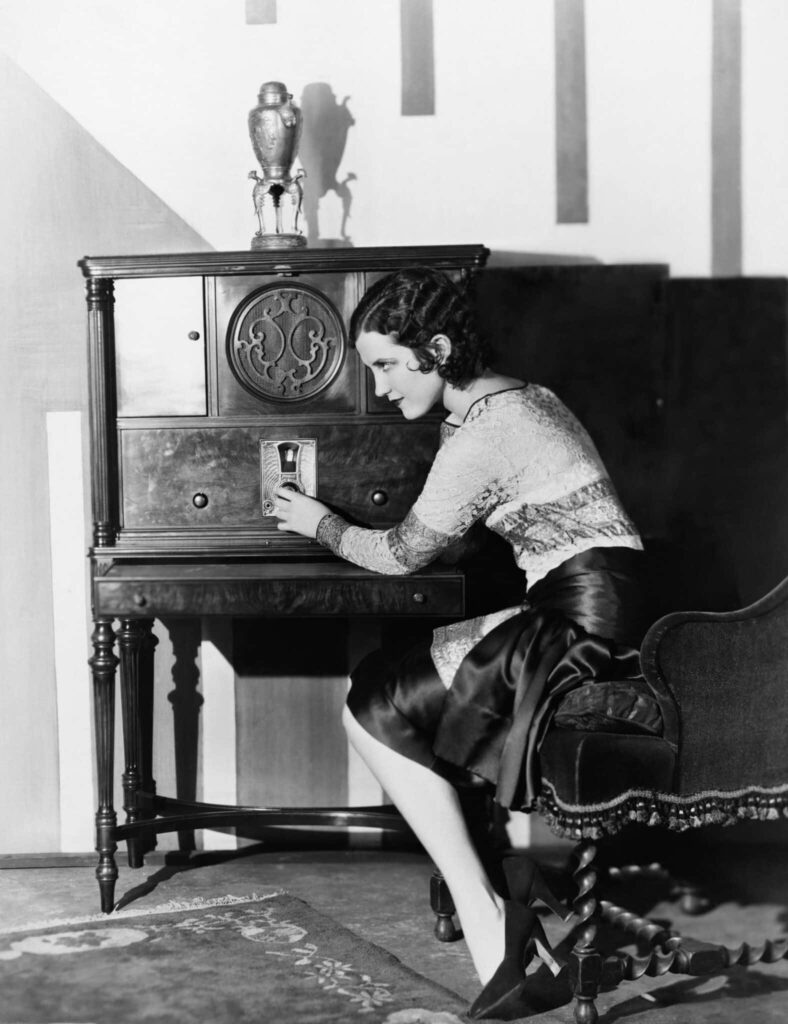Black and white, vintage photo of a woman tuning the radio