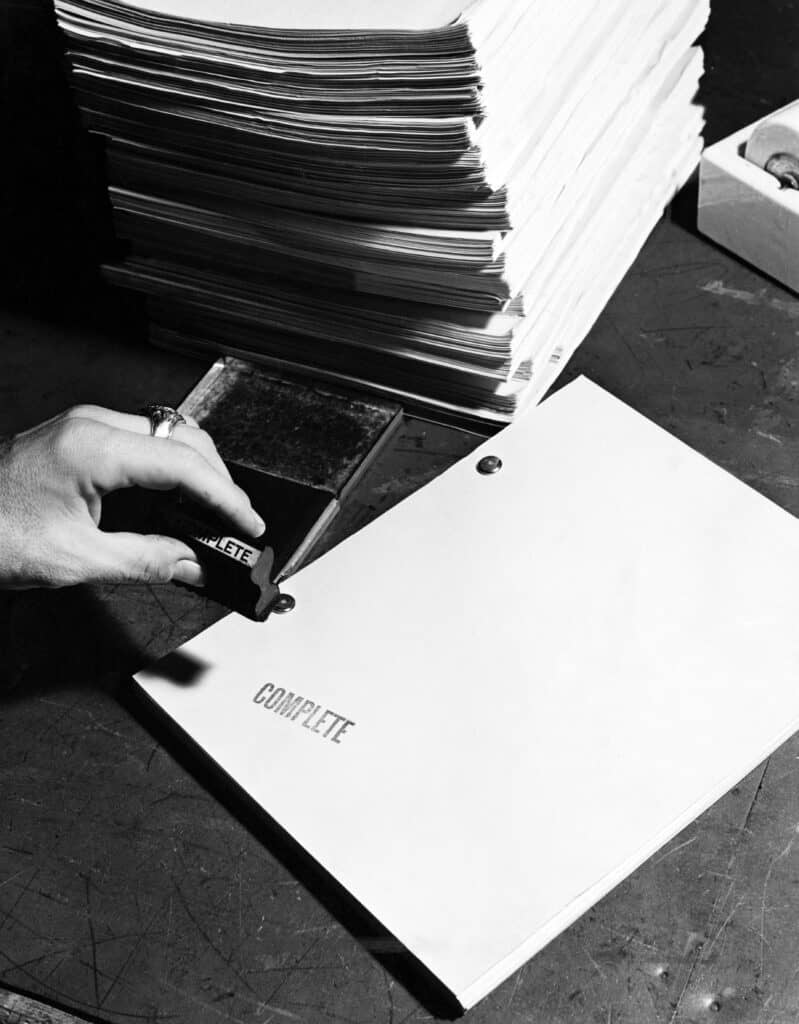 Black and white photo of a script being stamped 'complete'