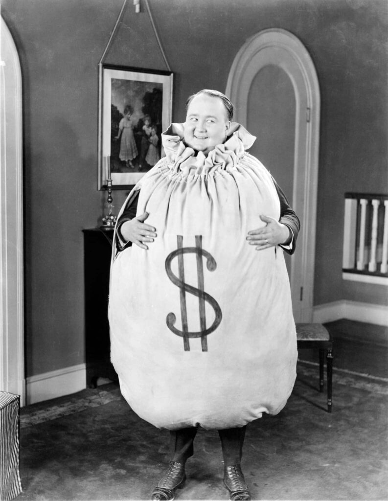 Black and white, vintage photo of a man holding an enormous sack with the 'dollar' symbol on it