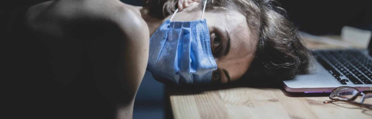 Woman in medical mask resting head on table near laptop, looking depressed.