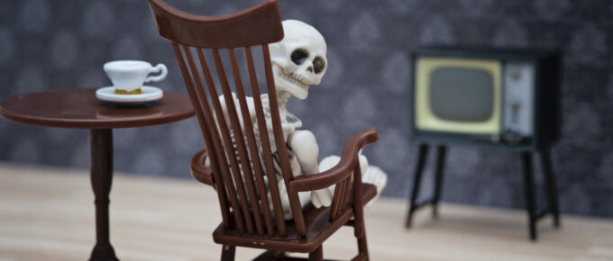 Skeleton in a rocking chair, trying to watch TV, and looking over his (its?) shoulder to the camera