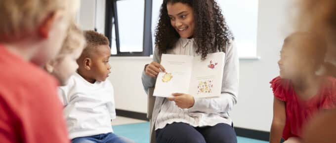 Black millennial woman teacher reading a storybook to her students.