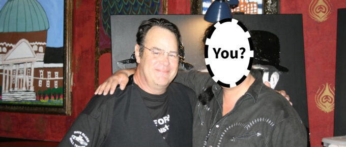 "An image of Dan Aykroyd with a second person whose face is 'blanked' out and it says ""You?"" over top"