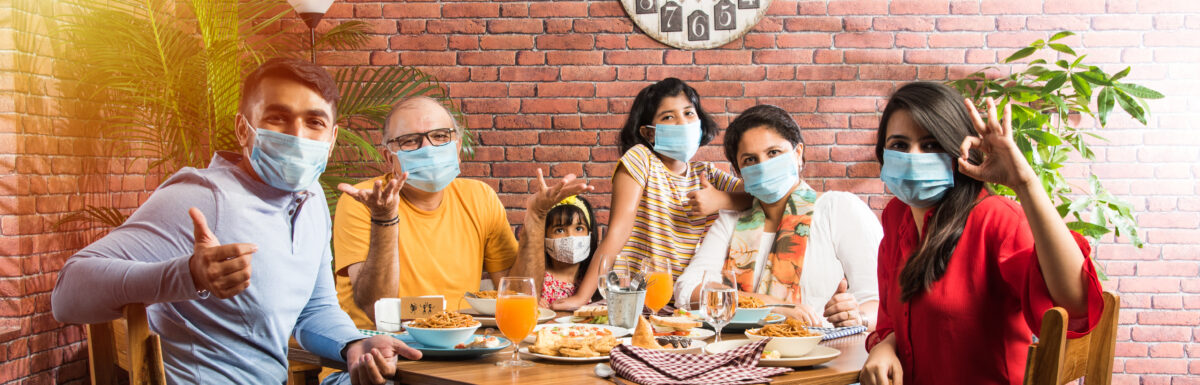 Family wears face masks while eating food in restaurant