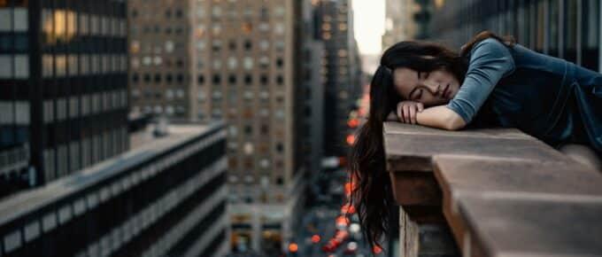 Woman resting head on balcony of skyscraper, sleeping