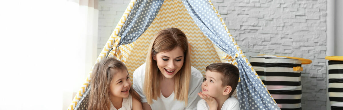 Nanny and little children reading book in tent at home