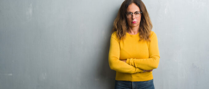 Middle age hispanic woman over grey wall wearing glasses skeptic and nervous, disapproving expression on face with crossed arms. Negative person.