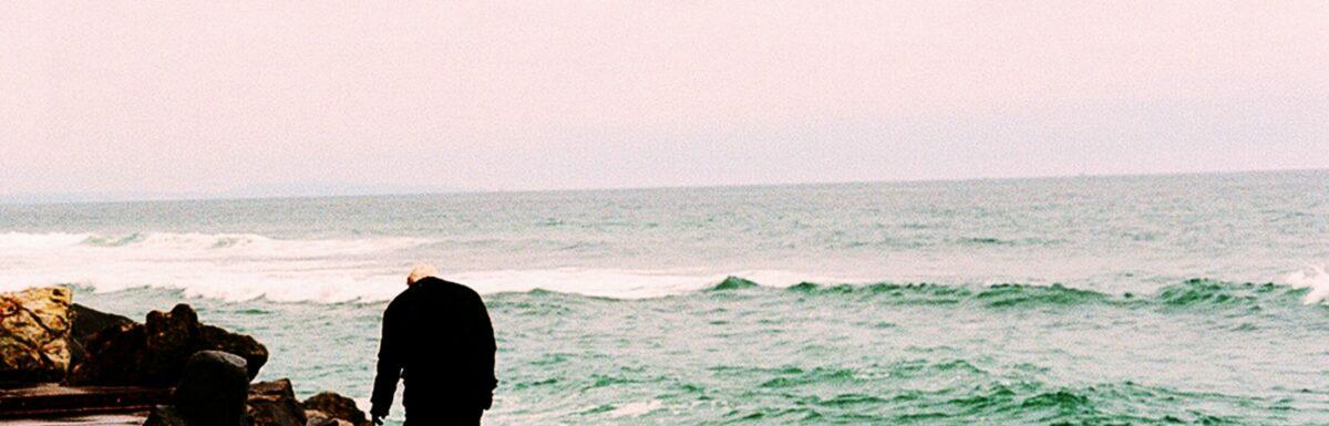 An elderly man stands on the rocks near the ocean
