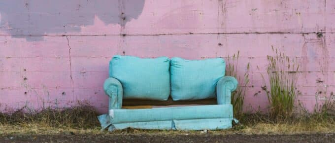 Ragged blue couch placed outdoors
