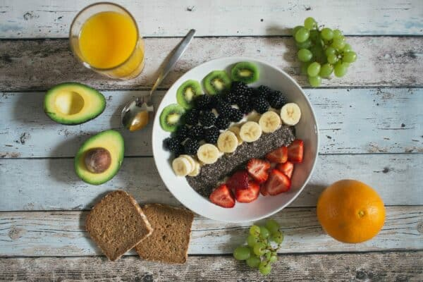 A plate of fruits and vegetables and juice