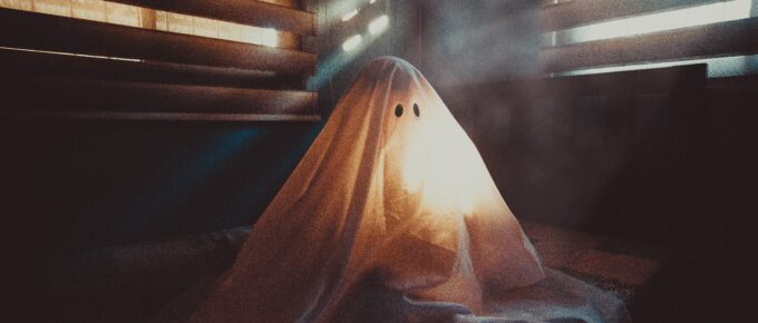 A ghost in a sheet sitting at the edge of a bed in the dark