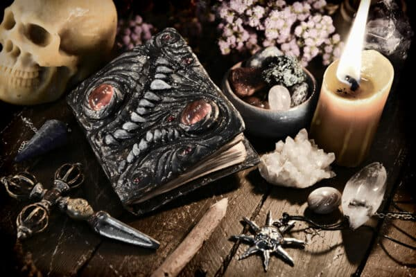 Scary evil book with skull and burning candle. Wicca, esoteric and occult background with vintage magic objects for mystic rituals. Halloween and gothic concept