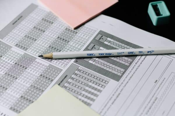 A Scantron multiple choice form, with pencils and sharpeners around