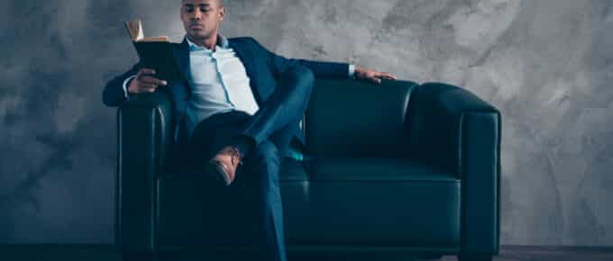 Sexy, Black professional man reading a book on a couch