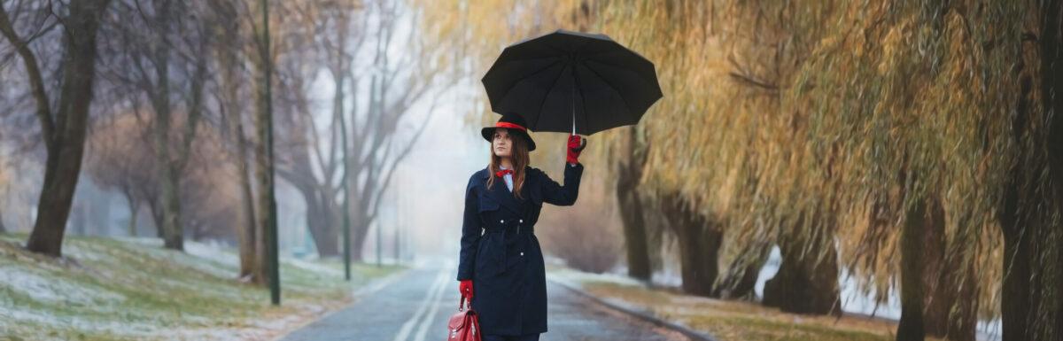 A girl in a hat walks in the rain. Mery Poppins goodbye!