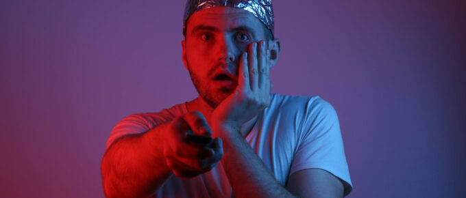 Surprised Bearded Man in a foil hat holds tv remote in red-blue neon light. Conspiracy
