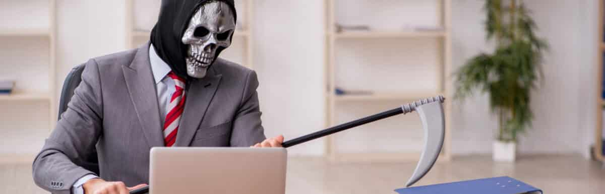 The grim reaper, in a business suit, at a desk
