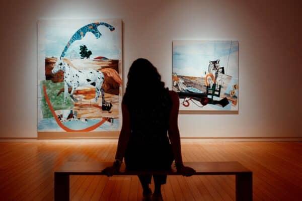 Woman sits in art gallery, looking at paintings