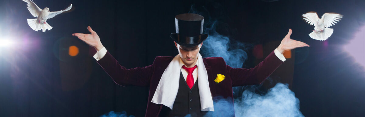 The magician with a two flying white Doves. on a black background. shrouded in a beautiful mysterious smoke