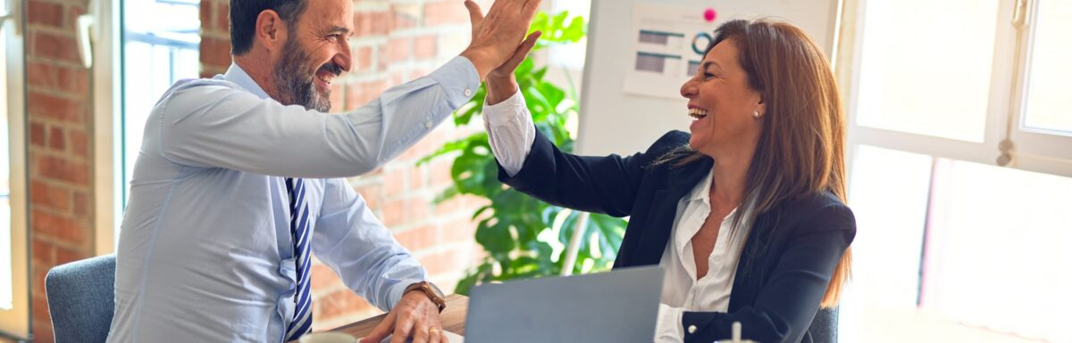 Two businesspeople smiling and high-fiving