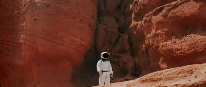 An astronaut on the surface of a red planet (or maybe it's just the red part of an otherwise verdant planet, how the hell should I know?)